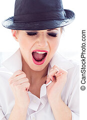 Shouting young businesswoman wearing man's shirt, hat in office
