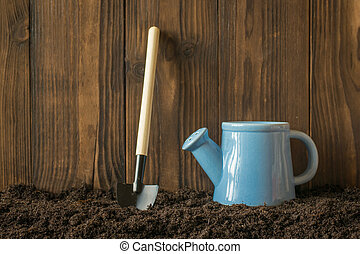 Shovel and watering can near a wooden fence on the ground.