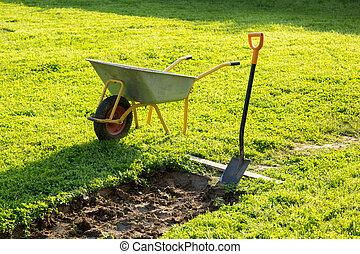 shovel and wheelbarrow on grass near the pit