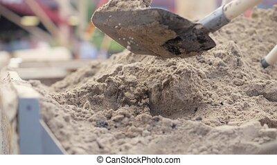 Shovel digging sand from large pile close up. Slow motion...