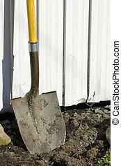 Shovel in earth against garden shed