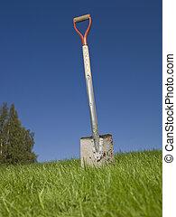 Shovel in green grass against a blue sky