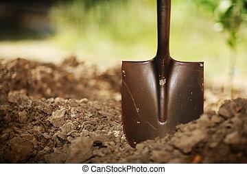 Shovel in soil. Close-up, shallow DOF.