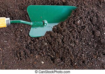 shovel in soil for flower and seedingses background