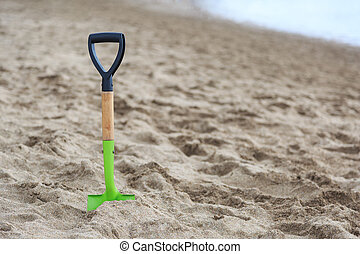 Shovel in the sand of a beach
