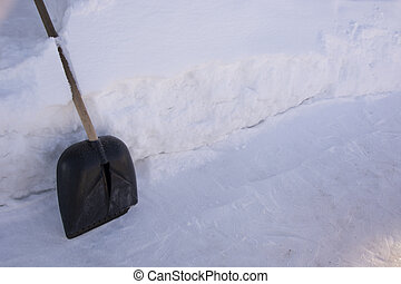 Shovel in the snow. High snowdrifts. Raking away the snow in the garden. There is a lot of snow in the garden in winter.