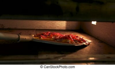 Shovel putting pizza into oven. Thin crust, vegetables and...