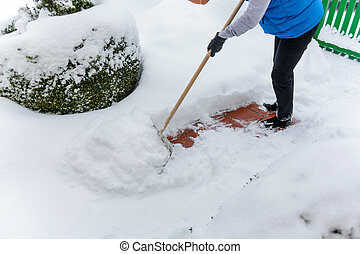 shoveling snow woman while - a woman shoveling the new snow...