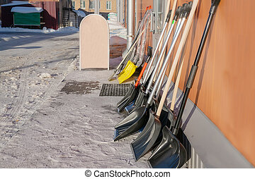 Shovels for clearing snow in winter are sold on the street. A variety of shovels stand along the wall outside on a Sunny winter day. Copy space