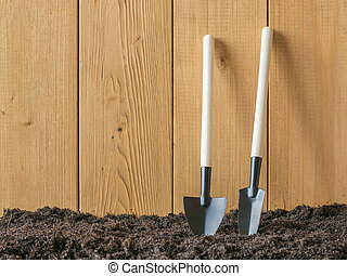 Shovels for digging and removing weeds near a wooden fence.