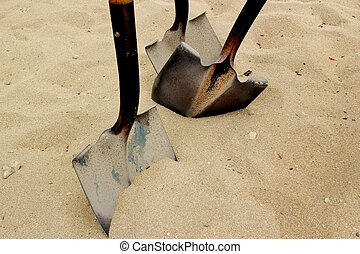 Shovels in the sand - Three old shovels stuck in the sand