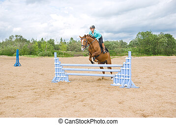 show jumping. girl riding horse and jumping