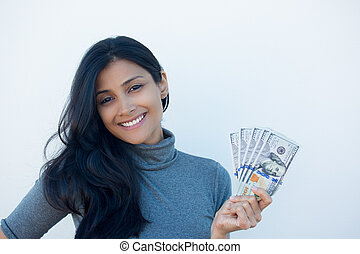 Closeup portrait, excited successful young business woman in gray shirt holding money dollar bills in hand, isolated white wall background. Positive emotion facial expression feeling. Financial reward