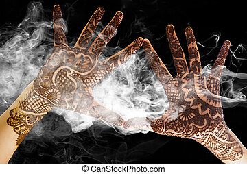 Show the beautiful Henna tattoo at the open hand with smoke and light