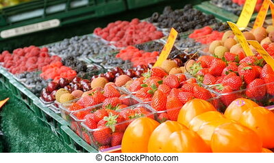 Showcase on open market with various berries of sweet...