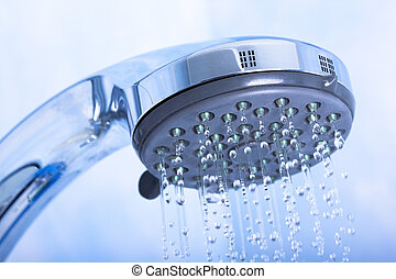 Shower head with running water on blue background
