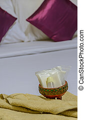 Shower set and yellow towel on white bed