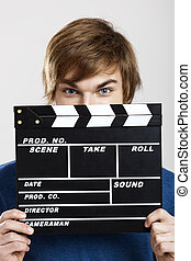 Showing a clapboard - Portrait of a young man peeking behind...
