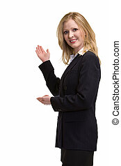 Attractive blonde woman in professional business suit standing sideways holding up hand as in showing something behind her standing on white