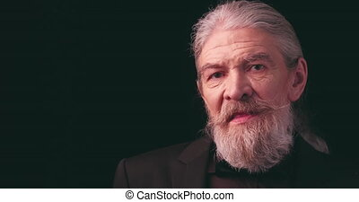 Showing facial expressions old man with long beard in dark business clothes looking at camera in semi-lit room on black. Old businessman. Toned footage. Prores 422.