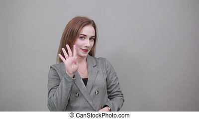 Showing four 4 fingers hand gesture, show the number three with hands, pointing up arm while smiling confident, happy. Young attractive woman, dressed gray jacket, with green eyes, light brown hair