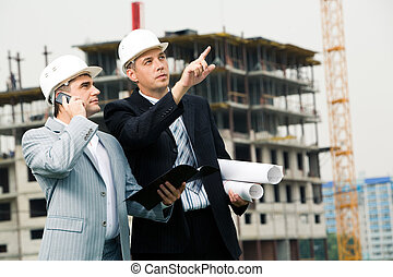 Photo of serious employee pointing at something with calling foreman standing near by