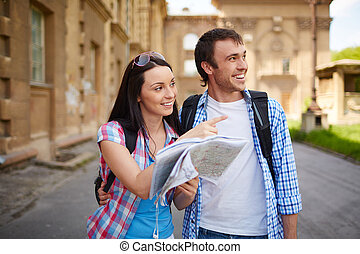 Couple of travelers with map deciding where to go sightseeing