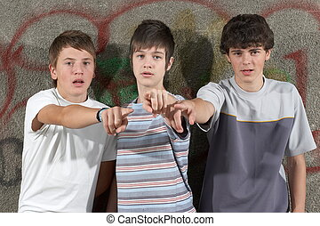 Three young boys showing something with their fingers