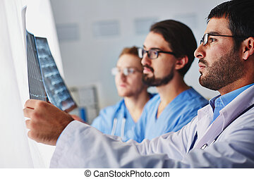 Showing x-ray - Portrait of young male doctors looking at...