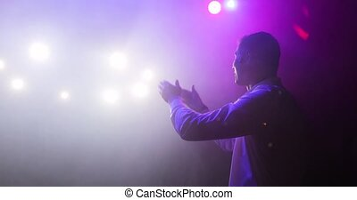 Showman comedian clapping hands on stage entertaining audience in spotlights.