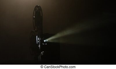 Shows movie in a projector in the smoke. Black background