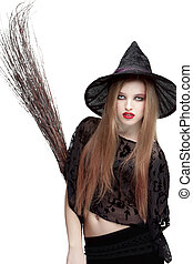 Showy young woman in witch costume with a broom - Showy...