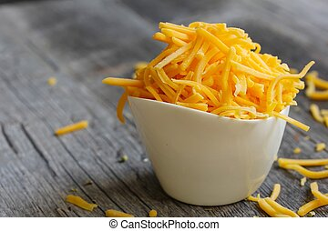 Shredded cheddar cheese in white cup  close up
