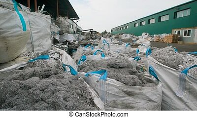 shredded metal garbage is packing in large white plastic...