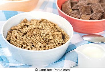 Shreddies - Whole grain wheat cereals in a bue bowl.