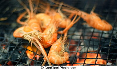 Shrimp are grilled and turned over using tongs. Night...