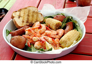 Shrimp boil with corn, sausage, potatoes, and bread.