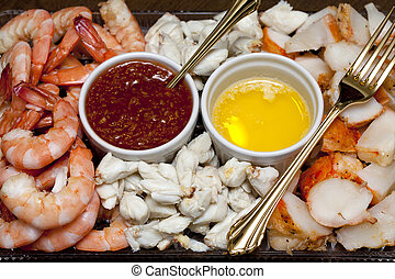 Shrimp, crab meat and lobster on a plate with cocktail sauce and butter