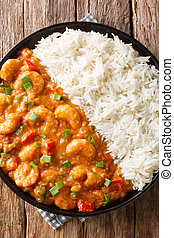 Shrimp Etouffee classic Louisiana stew is made with shrimp, onion, celery, and green pepper served with rice closeup on the table. Vertical top view