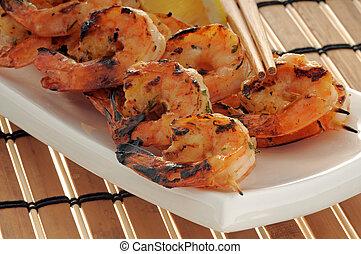 Shrimp - Grilled shrimp skewers closeup served with lemon.