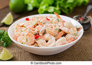 Shrimp in a creamy garlic sauce with parsley and lime in white bowl