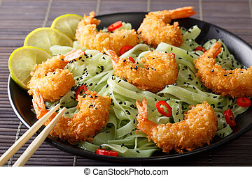 Shrimp in breadcrumbs with green pasta, chili pepper and...