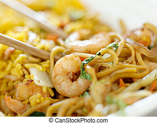 shrimp lo mein with fried rice with extremly thin focus and blurry background.