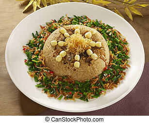 Shrimp lotus seed cakes on fried rice with sauteed onion on white plate