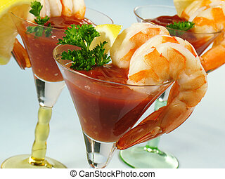 Chilled shrimp served with cocktail sauce in martini glasses.