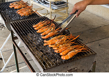 shrimp on the grill with hand