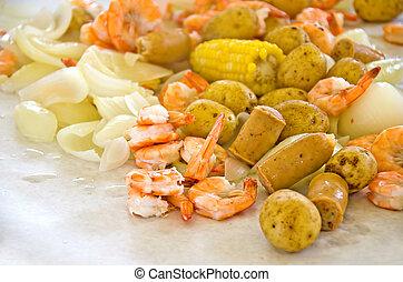 Shrimp, onions, sausage, corn and potatoes on white butcher paper for shrimp boil party.