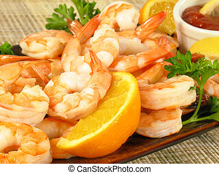 Chilled shrimp served with cocktail sauce, lemon wedges, and parsley.