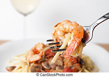 A delicious shrimp scampi pasta dish along with a glass of pinot grigio white wine. Shallow depth of field with focus on the fork and shrimp.