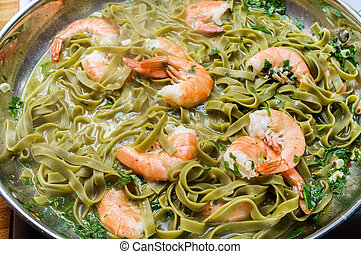 Cooking shell on shrimp scampi with green spinach pappardelle pasta in large pan